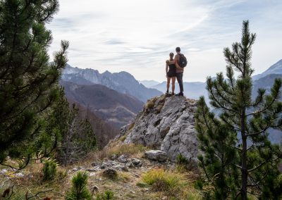 Selfie in the mountains of Teth, Valbona peak, Albania. Two people standing on a rock with mountains on the background.