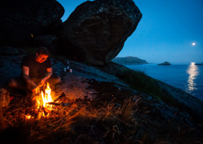 Making a bonfire in a cave close to the ocean in Norway. Moonlight reflecting on the sea.