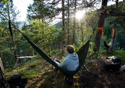 In a hammock with a sunset in the mountains of Norway.