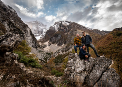 Group photo during a hike in Permet, Albania. High mountains on the background and some clouds and snow.