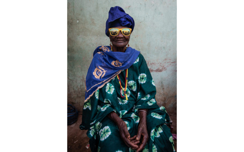 Old African woman wearing yellow sunglasses